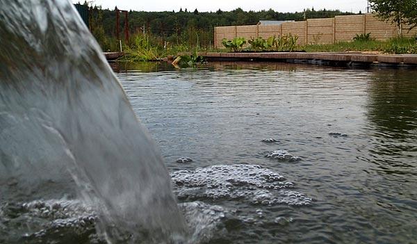 Вид пруда вдоль воды со стороны водопада